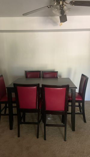 Black wooden dining table that extends with 6 red and black leather chairs for Sale in Maryland Heights, MO