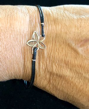 Pretty little silver plumeria and leather bracelet. Bracelet is small to medium. for Sale in Tolleson, AZ