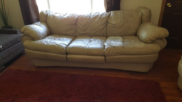Leather couch and loveseat with black covers