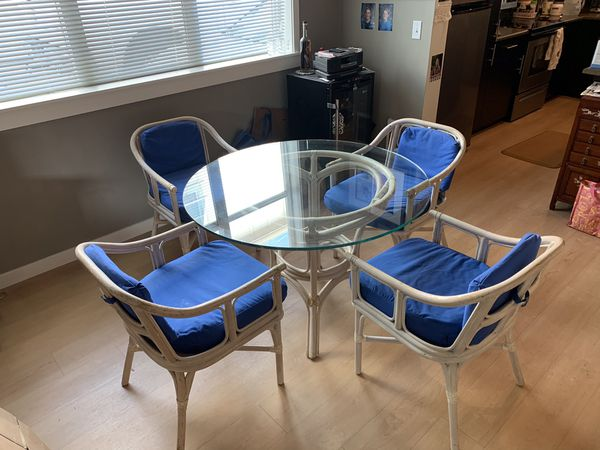Glass top bamboo table with four chairs. Have two sets.