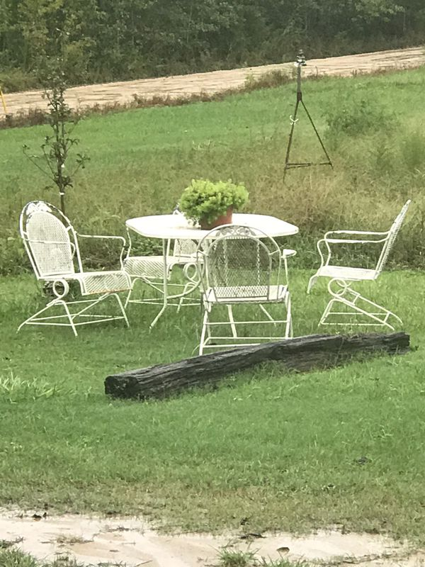 Vintage wrought iron mesh, large oval matching table and 4 coil spring rocker chairs, in good condition, for $450.00.