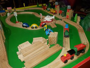 Kids Playing Table with a wooden train set 100 + pc.set.And a race track rug and The car's with it. for Sale in Runnells, IA