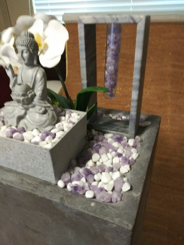 Beautiful one-of-a-kind Buddha fountain on pedestal with amethyst rocks an artificial flower