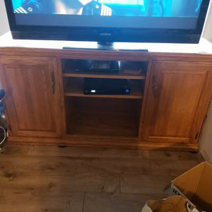 Nice oak TV stand now holding a 55 inch TV could hold larger one no problem for Sale in Bothell, WA