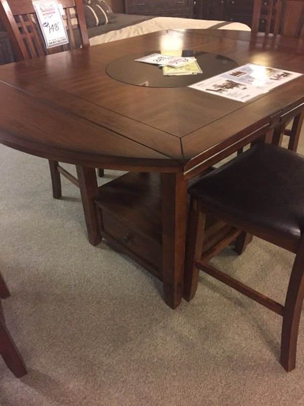 Solid oak wooden dinning room table with a circular granted top that rotates and with four chairs