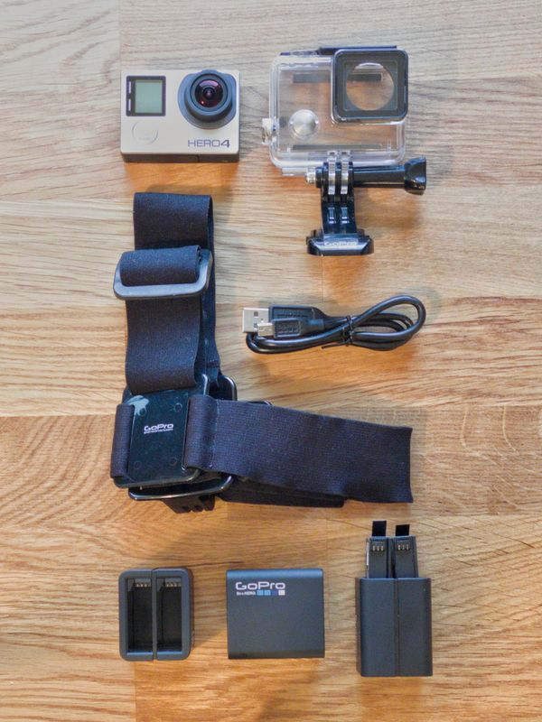 GoPro 4 with official accessories: waterproof case, 3 batteries, helmet mount, charging stations, and USB cable