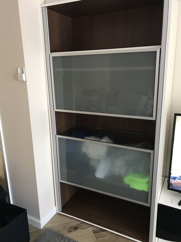 Big closet with a shelves . Part of shelves are wood and part are glass . Door are sliding up and down .