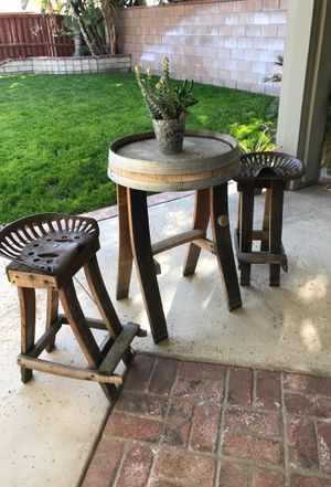 Wine Barrel table and two chairs with the tractor seats for Sale in Highland, CA
