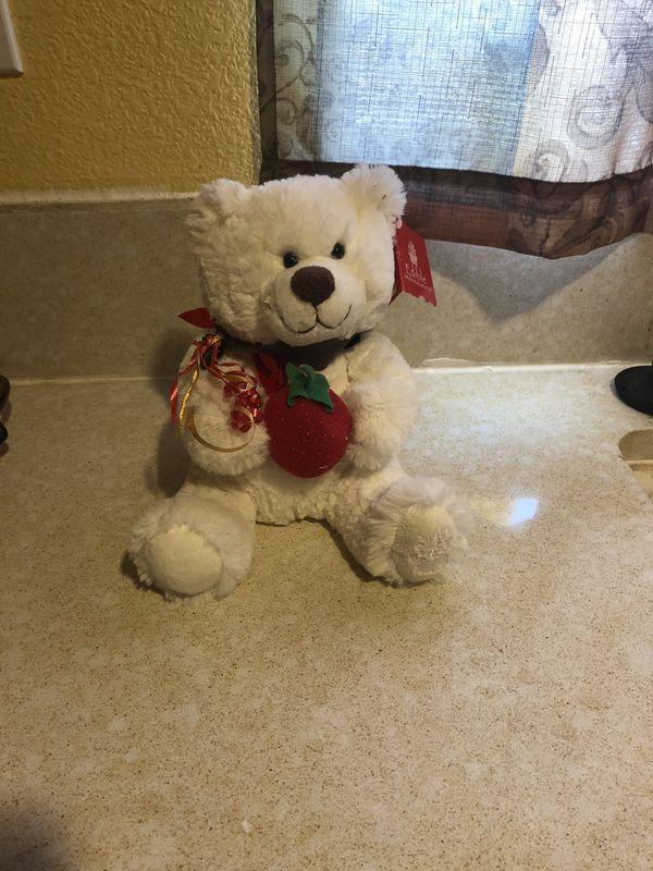Stuffed bear holding a strawberry