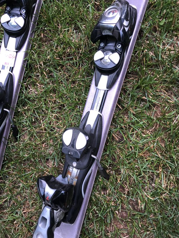 set of skis with poles,boots,helmet, and goggles
