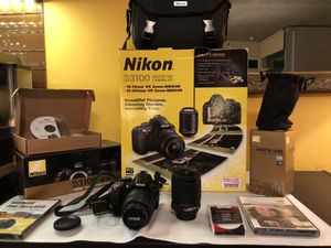 Nikon D3100 14.2 MP DSLR package with orig Nikkor 18-55 and 55-200 lenses and 2 carrying cases, users manuals, training videos, charger and extra fil for Sale in Chicago, IL