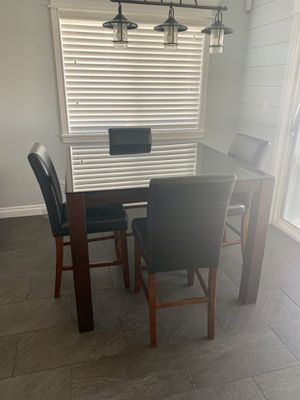 Tall glass top kitchen table with dark wood legs and 4 faux vinyl cushion chairs for Sale in Las Vegas, NV