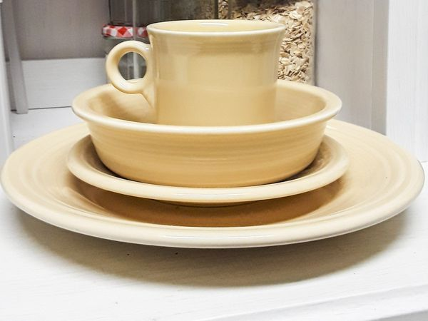 Complete place setting of ivory Fiestaware dishes