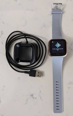 Fitbit versa rose gold with charging cable and grey band for Sale in Woodstock, GA