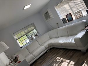 Designer White leather L-shaped wrap around couch for Sale in Miami, FL