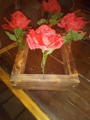 BEAUTIFUL FLOWER CENTERPIECE 4 FAKE ROSES AND BEAUTIFUL BURNED BASE $25 FIRM BEST PART IS YOU CAN CHANGE OUT THE FLOWERS MUST PICK UP for Sale in Phoenix, AZ