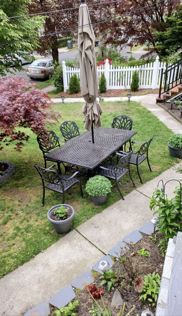 Cast Aluminum table With Six Chairs , Umbrella and Base included.