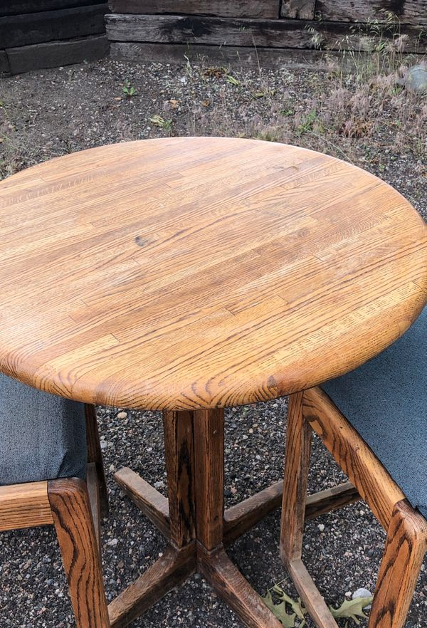 Round oak table with two matching stools