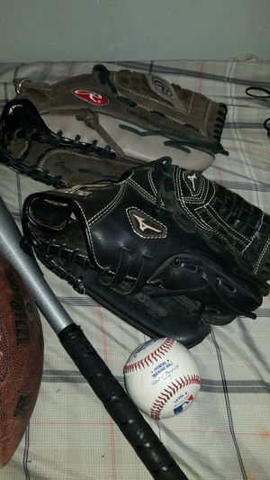 Baseball gloves, footballs, a bat and ball. for Sale in Culver City, CA