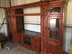 Large entertainment center. Three pieces. Real wood. Has DVD storage racks in both sides. And lights in shelves and in center piece over tv. Great co for Sale in Midland, TX