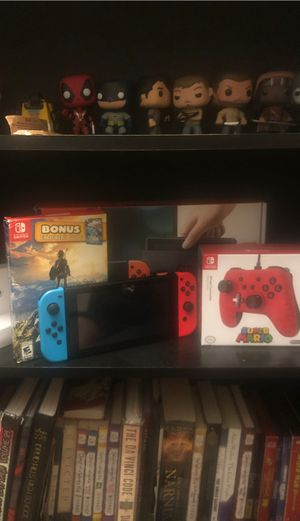 Nintendo switch to that includes everything in the box plus a controller with legend of Zelda breath of the wild game cart with super smash bro's ult for Sale in Decatur, GA