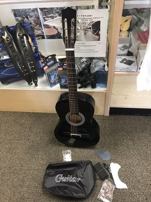 Black acoustic guitar, new in box, while supplies last $40 with bag, strap, extra strings and pick and pick guards. for Sale in Downey, CA