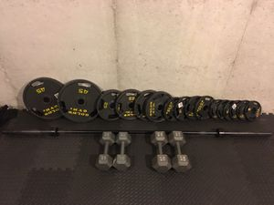 """260 lbs of olympic 2"""" weights plus 45lb bar. Also 25lb & 35lb dumbbells for Sale in Traverse City, MI"""