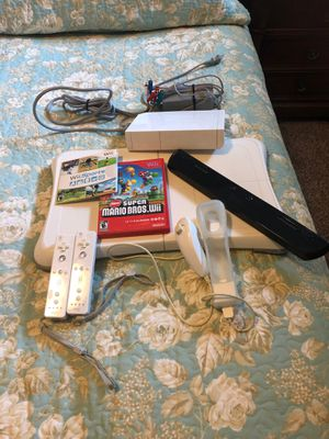 Wii device with 2 controllers, 1 nunchuk silicone skin, Mario Bro's game, & Wii Sports game. The only thing missing is the back of one controller (as for Sale in Flower Mound, TX