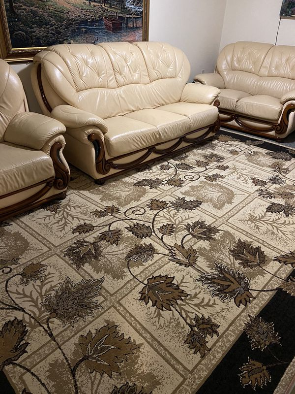 Tan/Brown Sofas, Tall Floral Arrangement, And Rug