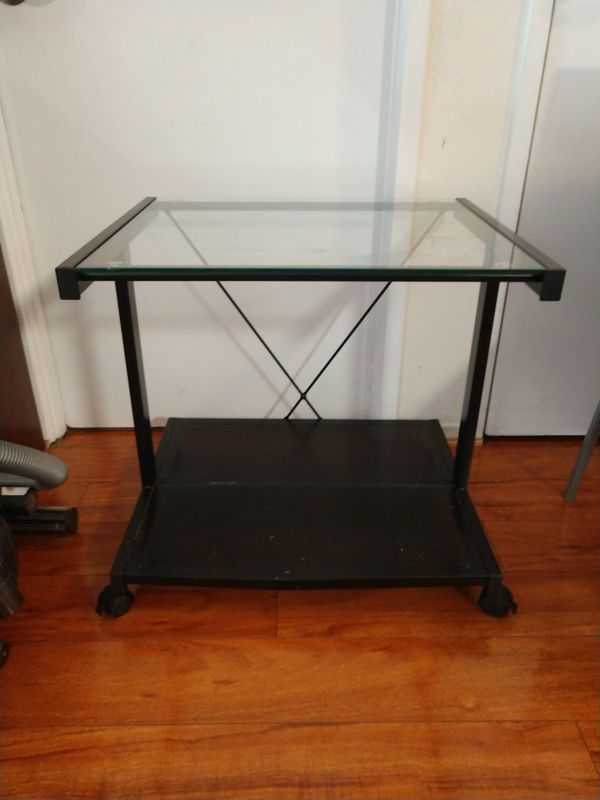 Small metal and glass TV stand on wheels