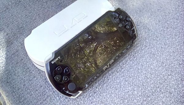 PSP game console with charger and 8 games and movies
