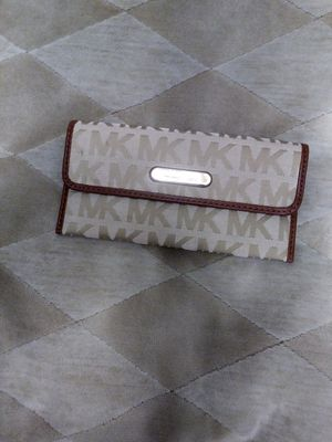 Authentic Michael Kors wallet made of material with a cognac color leather trim. Clean on the nside and out, no stains, snags, rips or discolorations. for Sale in Detroit, MI