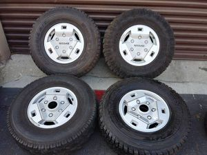 6 lug stock 15x7 aluminum nissan hardbody 4x4 rims and caps with tires for Sale in Montebello, CA