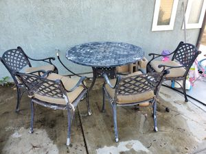 Outdoor metal table with chairs. Great restoration project, needs to be powder coated/painted. Middle hole for umbrella for Sale in Corona, CA