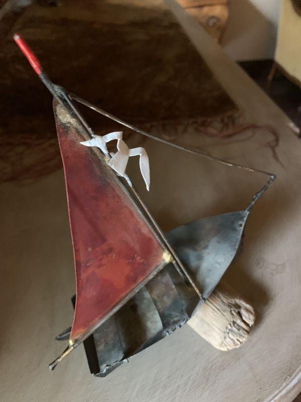 Vintage metal sail boat on drift wood
