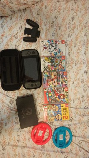 Nintendo switch, plus five games, two steering wheels and carrying case for Sale in Fresno, CA