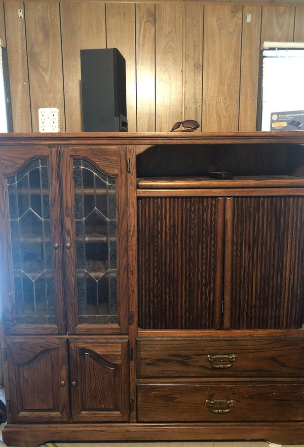 A dark wood entertainment center TV stand