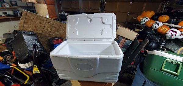 Coleman cooler with 4 cup holder on top of the lid.