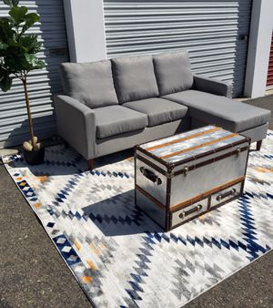 Brand new reversible grey upholstery sectional with Pier 1 aluminum coffee table trunk for Sale in San Diego, CA