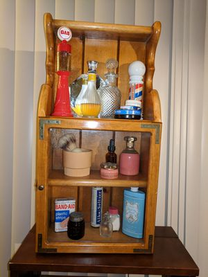 Old fashioned medicine cabinet with collectible vintage Avon and other brand name antique bottles. for Sale in Colorado Springs, CO