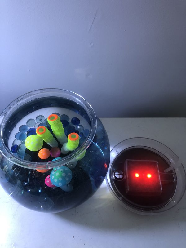 1 gallon fish tank with LED lights, glow in the dark accessory, and marble rocks