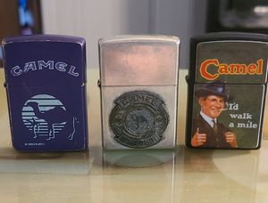 Vintage Zippo Joe Camel lighters. Purple one is 1993, the I'd walk a mile is 1995, and the other one is the 85th Anniversary one. for Sale in Greenville, SC