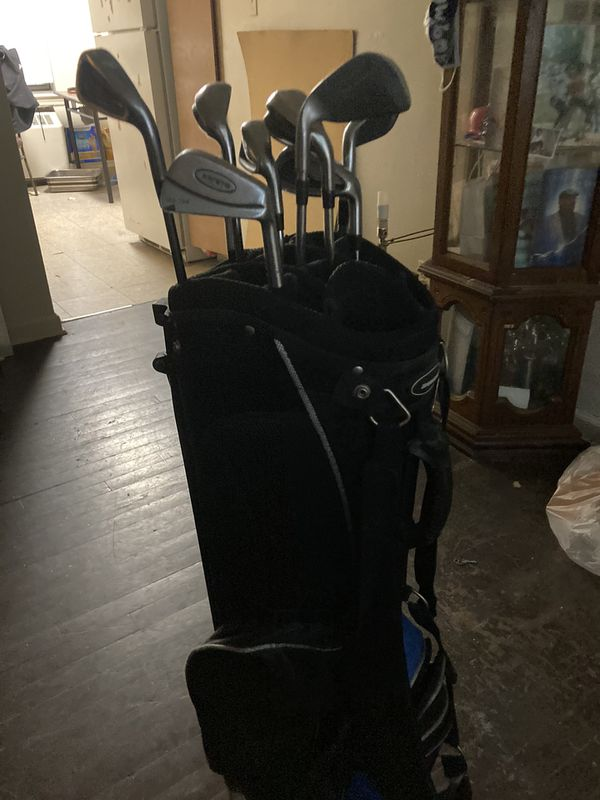 Golf clubs with bag and fishing rod