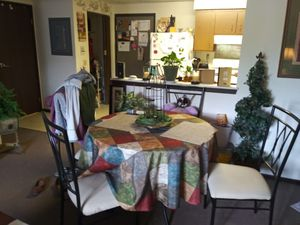 Black metal dining table with glass today. 4 ivory colored cushioned chirs for Sale in Erie, PA