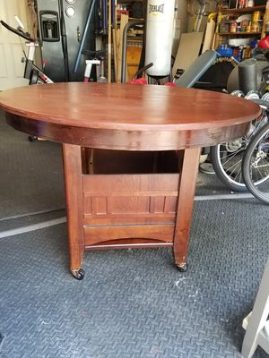 """Wood Kitchen table, oval with leaf, 60 inches. Round 42""""no leaf. Storage under, on wheels. Great shape but light Mark's on table top. 40.00 for Sale in Spring, TX"""