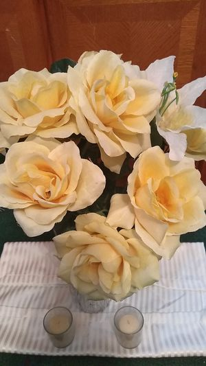 set for $12 beautiful spring/summer color artificial yellow flowers in a nice clear glass vase includes 2 small vanilla scented candles $12 for Sale in Cleveland, OH