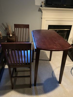 "Beautiful brown wooden bar table with 2 matching chairs. Collapsible leafs make table round and 36"" for Sale in Alexandria, VA"