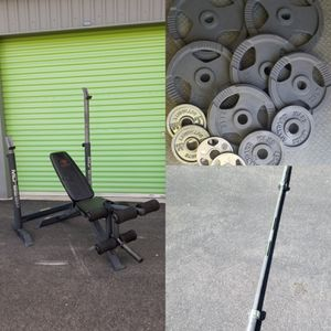 Weight bench adjustable with Olympic weights and barbell 45x35x25x10x5x2.5 for Sale in North Las Vegas, NV