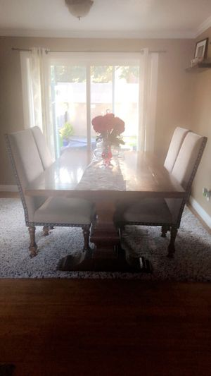 Sturdy, 6 seater dining room table. Dark finish with a extension leaf. 4 regular chairs with 2 captain chairs for a total of 6 chairs. for Sale in Tacoma, WA