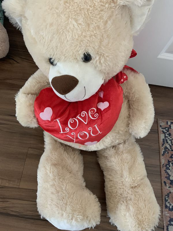 """plush tan teddy bear holding a red heart that says """"I Love You."""""""